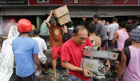 Người dân Tacloban mang đồ lấy cắp ra khỏi một cửa hàng