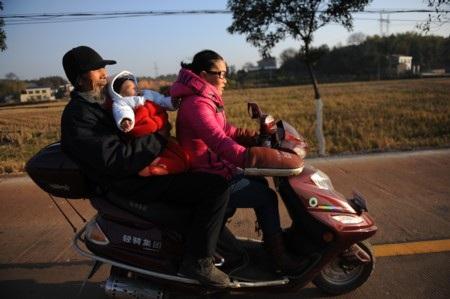 Cô Zhang chở chồng và con bằng xe máy