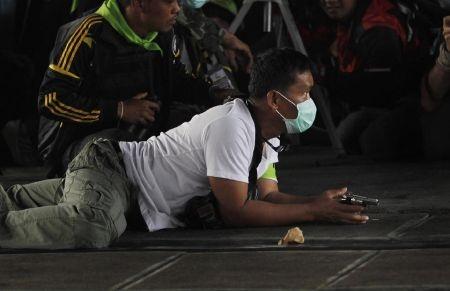 Một người biểu tình chống chính phủ ẩn nấp sau khi nổ súng vào đoàn người tuần hành ủng hộ bầu cử