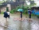 Chủ tịch phường mặc váy đứng trên bè cho người kéo qua vùng nước ngập