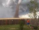 Người đàn ông thản nhiên cắt cỏ dù lốc xoáy sau lưng