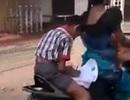 Cậu bé vừa ngồi sau xe máy vừa thoăn thoắt làm bài tập về nhà