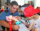 Hải quân Hoàng gia Canada cùng trẻ nhiễm chất độc da cam tô màu, đọc sách