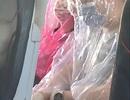 Bọc người kín mít bằng áo mưa trong suốt chuyến bay vì sợ Covid-19