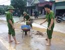 Công an đội mưa dọn bùn đất trên đường
