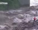 Người đàn ông đương đầu với dòng nước lũ cuồn cuộn