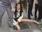 Vừa đi vừa dùng điện thoại, cô gái xinh đẹp lọt chân xuống cống