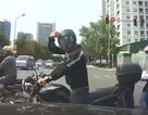 Chen ngang trước mũi ôtô, người đi môtô đưa kí hiệu lạ với tài xế