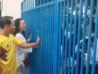 Thầy cô đứng trước cổng trường giữ điện thoại, động viên sĩ tử