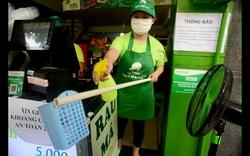 Nhân viên quán nước dùng gậy tự chế đưa tiền cho khách trong mùa dịch