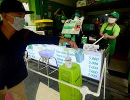 Sợ lây nhiễm, nhân viên quán nước dùng gậy tự chế đưa tiền cho khách