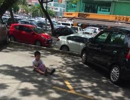 Mẹ bắt con ngồi giữa sân nắng để giữ chỗ đậu xe