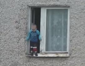 Thót tim em bé nghịch ngợm treo mình ngoài cửa sổ tầng 8