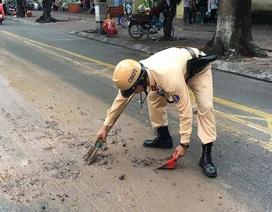 CSGT Hà Nội dừng xe thu dọn bùn đất vương vãi trên đường
