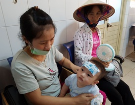 Bố mẹ lếch thếch mang theo quạt, nón đưa con đi khám bệnh ngày nắng nóng