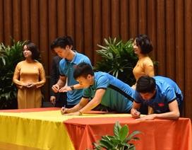 Tuyển thủ U23 cùng ký lên lá cờ Chủ tịch Quốc hội mang về từ Lũng Cú