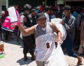 Chủ cửa hàng mở cửa cho người dân vào lấy đồ sau thảm họa ở Indonesia