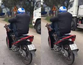 Nam thanh niên lái xe máy bằng chân, tay bấm điện thoại