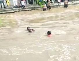 """Xem dân làng tạo """"dây chuyền người"""" giải cứu bé gái giữa nước lũ cuồn cuộn"""