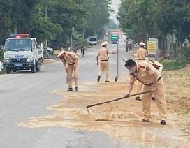 CSGT mượn chổi dọn cát sỏi rơi vãi trên đường