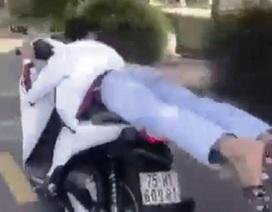 Nam thanh niên nằm trên yên lái xe máy lạng lách, đánh võng