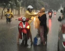 Cảm động hình ảnh cô gái dừng xe, mặc áo mưa cho bà cụ không quen