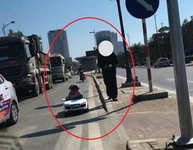 Cháu bé ngồi trong ô tô đồ chơi chạy trên đường phố Hà Nội
