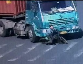 Người đi xe đạp thoát chết thần kỳ dưới bánh xe container