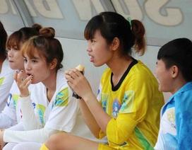 Cầu thủ nữ ăn bánh mỳ, chờ nhân viên tát nước để được đá bóng