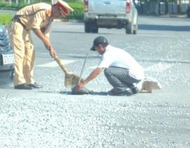 CSGT cùng người dân cặm cụi dọn đá dăm trên phố