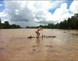 Khỏa thân liều lĩnh bơi thuyền qua sông đầy cá sấu