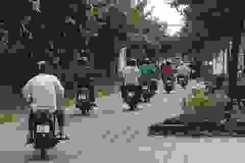 Xe cộ tấp nập chạy trên vỉa hè gần trụ sở cảnh sát giao thông