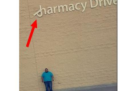 Chàng trai đứng chờ tấm bảng hiệu rơi vào người để được nhận tiền bồi thường