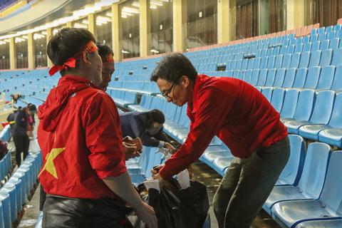 Phó Thủ tướng Vũ Đức Đam tham gia dọn rác sau trận đấu tại Mỹ Đình
