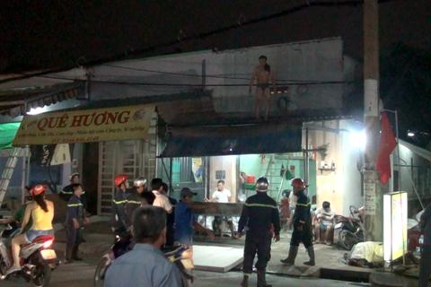 Người đàn ông cởi quần áo, trèo lên nóc nhà cố thủ