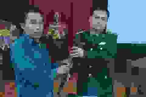 Một người dân bàn giao súng quân dụng và đạn
