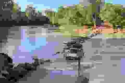 """Lái xe băng qua khúc sông """"tử thần"""", chẹt lên lưng cá sấu"""