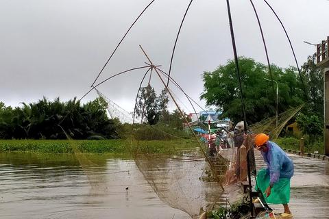 Người dân đổ ra đường giăng lưới bắt cá giữa lũ lớn