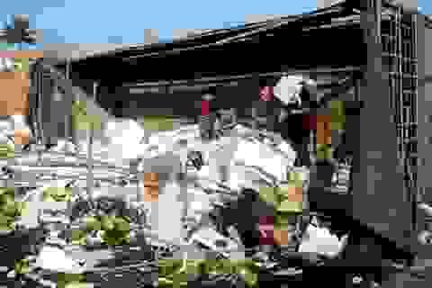 Người dân giúp tài xế xe tải thu gom hoa quả bị đổ ra đường