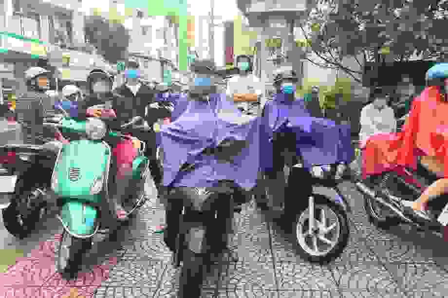 Phụ huynh Sài Gòn đội mưa chờ con thi xong môn Toán